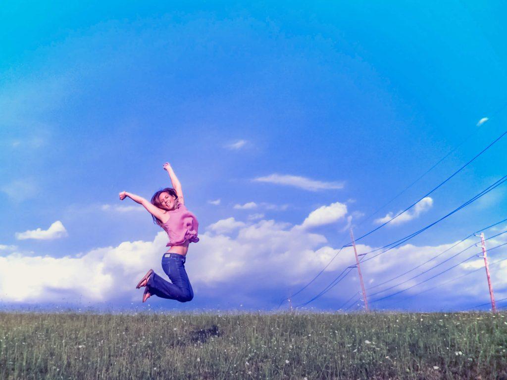 Illustratie: foto van een jonge vrouw die lachend in de lucht springt. De foto hoort bij de pagina over zelfwaardering en zelfrespect en is gemaakt door Marcy Kellar.